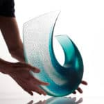 Glass sculpture by Galia Amsel with hands for scale