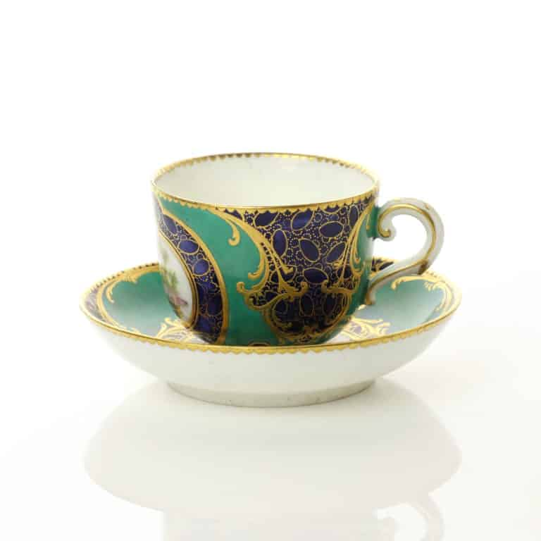Sèvres cup and saucer with dark blue and green grounds with caillouté and scroll gilding, and birds in landscapes, 1759