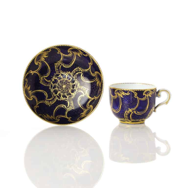A Sevres small cup and saucer dark blue grand swirling gilding