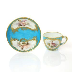 A Sèvres Cup & Saucer (gobelet Hébert & soucoupe) bleu céleste, putto in clouds, factory marks, date letter D for 1757, painter's mark M for Morin,