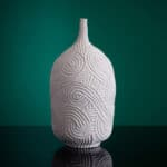 A carved porcelain vase by andrew wicks on a green background